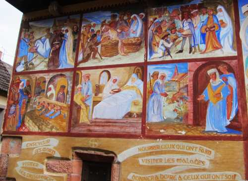 A gauche des trois morte et des trois vifs, les fresques évoquent les attitudes à adopter pour bien passer l'épreuve du Jugement dernier : visiter les malades, les prisonniers, nourrir ceux qui ont faim...