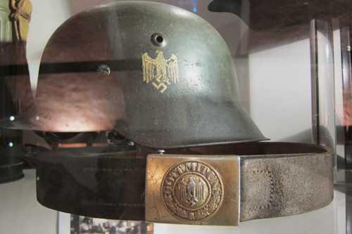 """Un casque allemand et le ceinturon avec l'inscription """"Gott mit uns"""" enserrant l'aigle allemand et la croix gammée."""