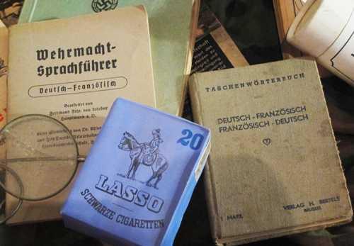 Des cigarettes allemandes et le dictionnaire franco-allemand, en usage dans la Wehrmacht.