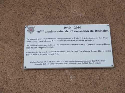 Sur la façade du bâtiment, cette plaque rappelle l'évacuation de Rixheim, les 17 et 18 mai 1940, évacuation qui est à l'origine du jumelage entre Rixheim et le canton de Valence-sur-Baïse dans le Gers.