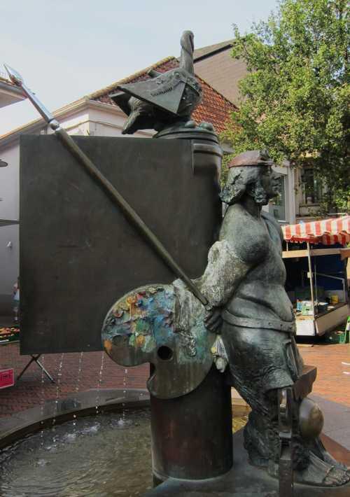 La fontaine est surmontée d'une oie, symbole de l'industriede la plume.