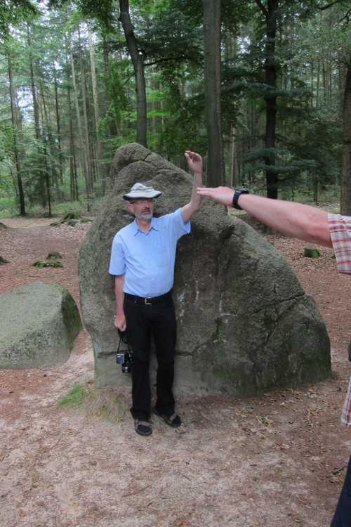Werner Steinke indiquant la hauteur de terre qui recouvrait le monument funéraire.