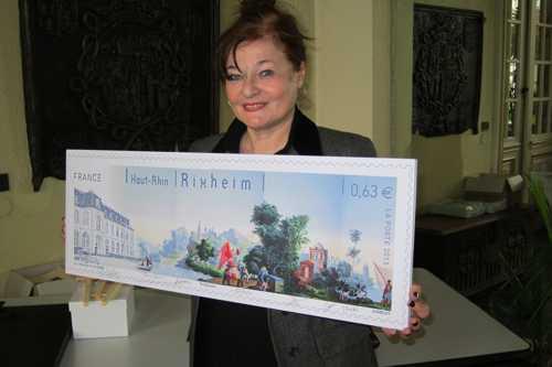 Simone haegy, vice-présidente de la SHR, présentant la maquette du superbe timbre de Rixheim.