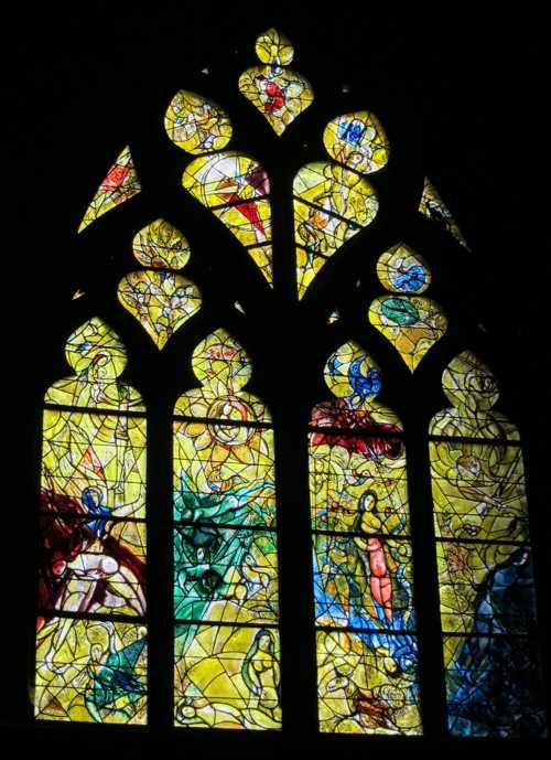Le vitrail de Marc Chagal dans le transept gauche (1963): de gauche à droite, la création d'Adam et d'Eve, le paradis terrestre, le péché originel et Adam et Eve chassés du paradis.