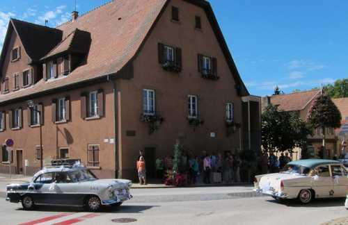 Devant l'ancienne mairie, passage de voitures anciennes, à l'occasion d'un mariage célébré le même jour.