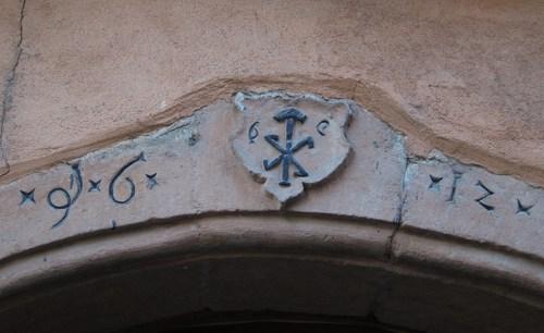 Sur un linteau de porte, daté de 1612, l'emblème du tonnelier : deux pinces et un maillet.
