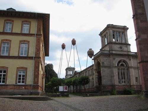 A gauche, le Dampfbad, élevé de 1846 à 1851 par Heinrich Hübsch et à droite, l'arrière du Friedrichsbad, construit à partir de 1877 par Karl Dernfeld. La scupture contemporaine des trois amphores sur leurs échasses, oeuvre de Franz Stühler évoque le passé romain de Baden-Baden et évoque aussi l'ancien Musée des Antiquités qui précédait le Dampfbad.
