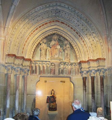 Dans le tympan, le Christ est entouré de Saint Pierre, à sa droite, et de Saint Paul, à sa gauche. Le linteau illustre une parabole du Christ : du côté gauche, il accueille les vierges sages, prévoyantes qui ont encore de l'huile dans leurs lampes, mais à droite la porte reste fermée aux vierges insouciantes. La statue de la Vierge est dite ouvrante et pouvait accueillir un ostensoire, une relique. Ces staures furent interdiyes âr le Concile dd Trente et elles sont aujourd'hui très rares.Ces