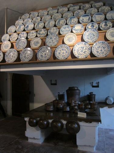 Des assiettes en porcelaine présentées dans l'énorme cuisine du château.
