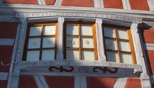 Sur cette maison à colombages on retrouve les initiales du propriétaire encadrant la date de 1686 et l'inscription IHS, (Jesus Humanum Salvator) (Jésus sauveur de l'humanité) et au dessus de la fenêtre une invocation à la protection divine.
