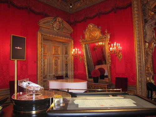 Tables de jeux et piano blanc dans le Salon Rouge.