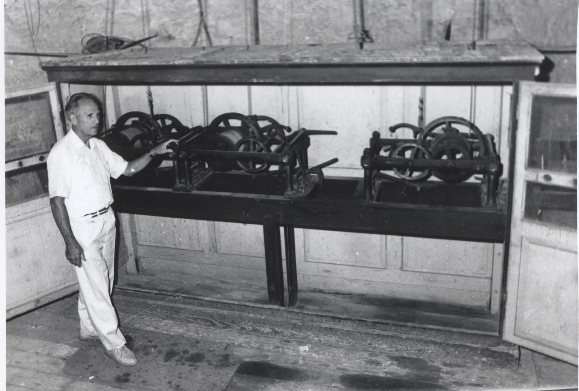 Léon Lizler devant le mécanisme de l'ancienne horloge du clocher.