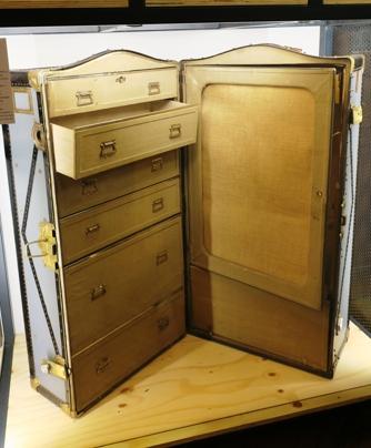 Une malle armoire de la marque américaine Innovation, vers 1900. Cette maison mit au point, vers 1895, les premières wardrobes, avec un éventail de cintres, permettant le transport de vêtements dans les meilleures conditions.