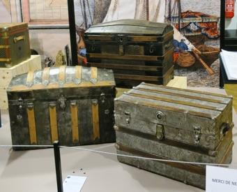 Deux malles bombées et une malle plate, toutes de fabrication américaine, en métal embossé, bois et cuir.
