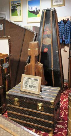 """Une malle plate de 1900 de la maison Moynat avec sa publicité : """"Le bagage Moynat ne craint rien, il se défend et résiste bien, parce qu'il est solide"""". Ces bagages étaient garantis 5 ans. A l'arrière, une malle pour violoncelle et pour contrebasse."""