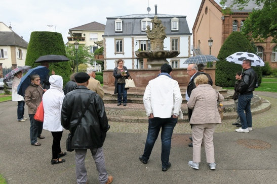 Devant la fontaine de l'abbaye de Surbourg transposé ici en 1886 par le maire Xavier Nessel, sur l'emplacement de l'ancien cimetière de l'église Saint Georges, désaffecté depuis 1788.