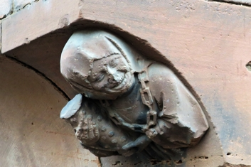 Le buste représente une jeune femme souriante tenant la mesure à vin utilisée à Haguenau et autour du cou, elle porte l'emblème de la ville, la rose quintefeuille.
