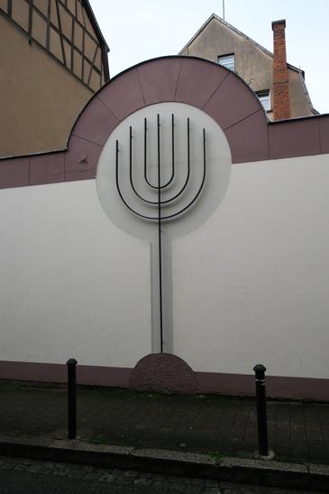 Une menorah, le chandelier à 7 branches, orne le mur d'enceinte de la synagogue.